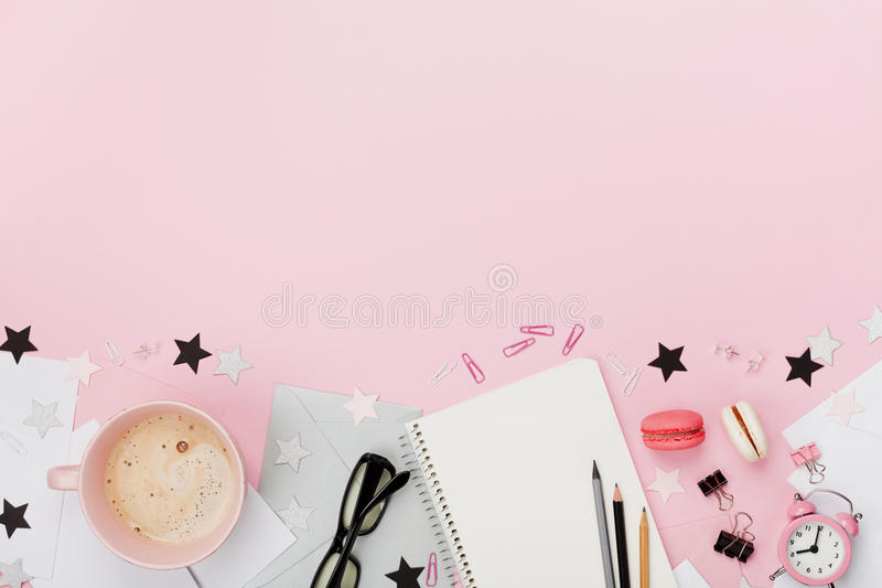 Fresh coffee, macaron, office supply, alarm clock and notebook on pink pastel table top view. Flat lay style. Cozy breakfast. royalty free stock images