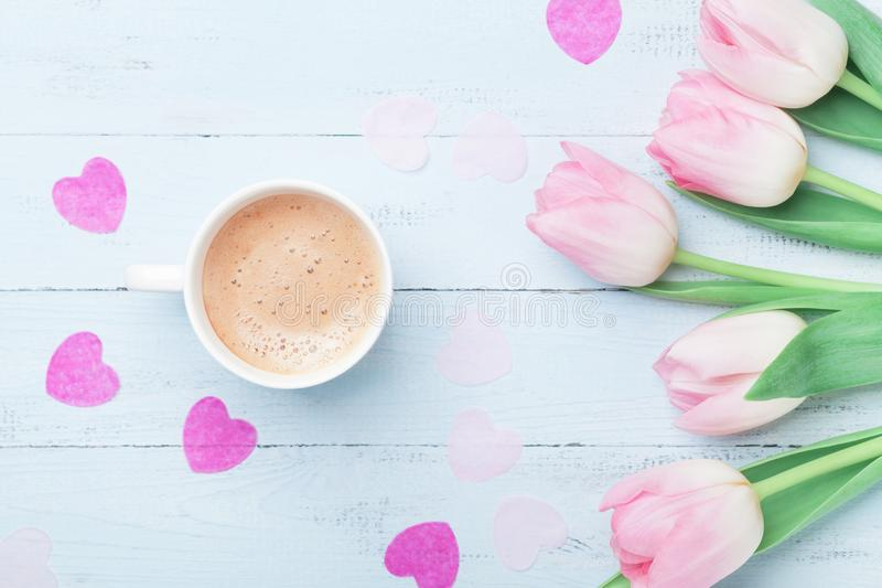 Fresh coffee and pink tulip flowers on pastel background top view. Beautiful spring breakfast on Mothers or Womans day. Flat lay. stock images