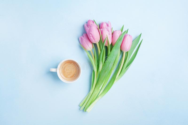 Fresh coffee and pink tulip flowers on pastel background top view. Beautiful spring breakfast on Mothers or Womans day. Flat lay. Fresh coffee and pink tulip stock photography