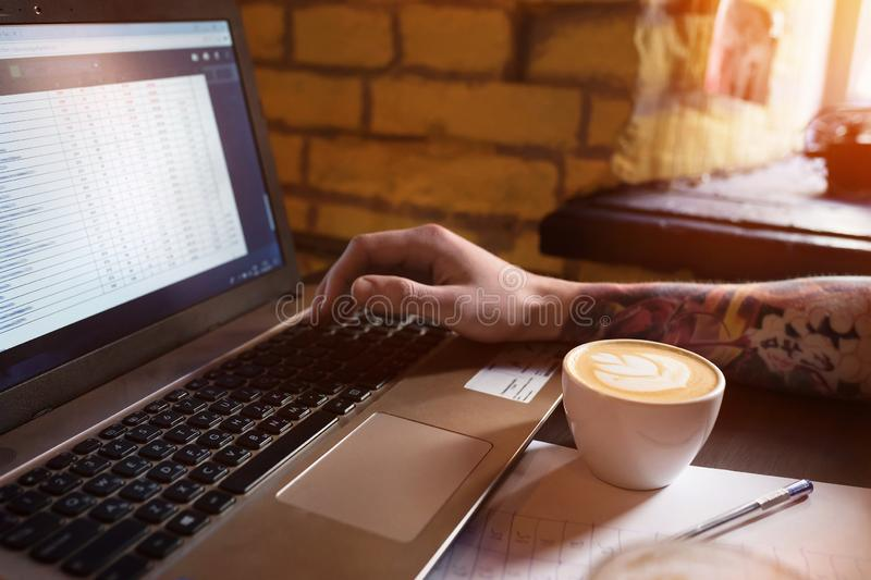 Fresh coffee for wonderful ideas. A man working on a notebook in a cafe stock photo