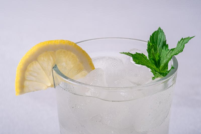 Fresh cold clear water drink in glass with ice cubes, lemon slice and mint leaf, on white gray background, macro stock photo