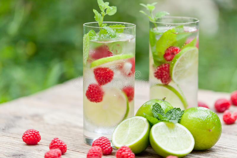 Fresh cold drink water ice cubes peppermint lime raspberry. Outdoor summer stock photo