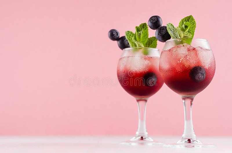 Fresh cold fruit cocktails in two elegant goblets with ice cubes, blueberry, green mint on pastel pink color background and white. stock photos