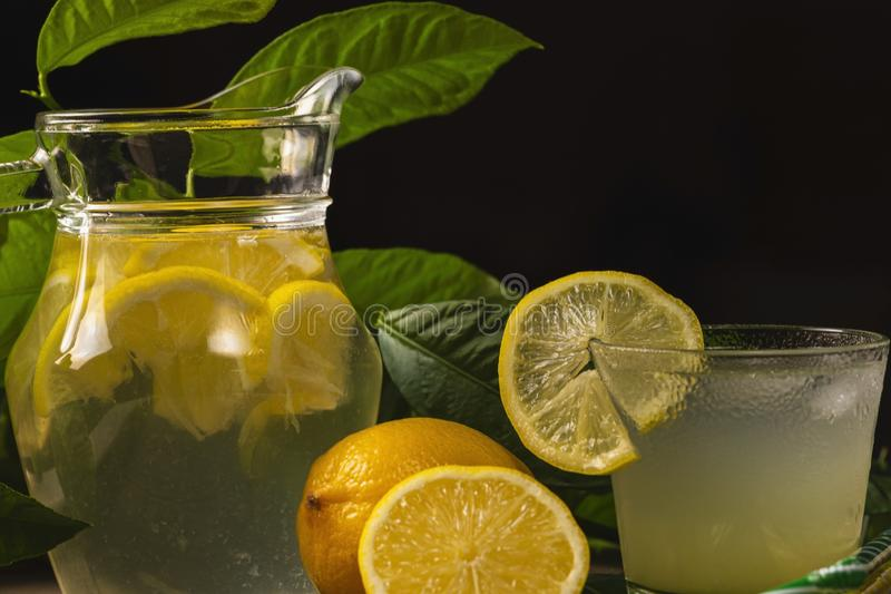Fresh cold lemonade with lemon slices on pitcher, black background with copy space stock photos