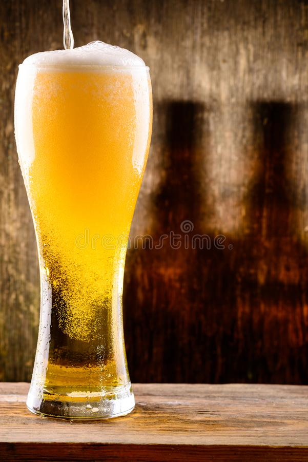 Fresh cold light beer pouring into glass with drops of water on royalty free stock images