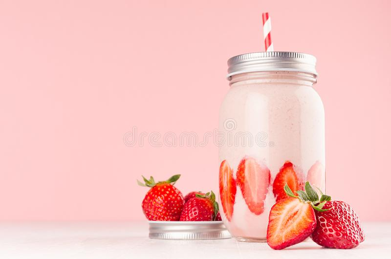 Fresh cold milkshake in hipster jar with cut ripe berries, striped straw, silver lid in elegance pink kitchen interior, closeup. royalty free stock photography