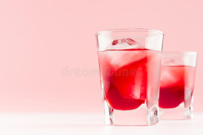 Fresh cold red summer fruit cocktails with ice cubes in elegant modern kitchen interior in light soft pastel pink color. Fresh cold red summer fruit cocktails stock photo