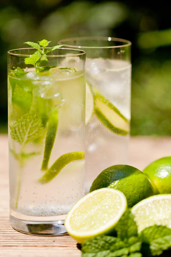 Fresh cold refreshment drink mineral water soda with lime and mint. On wooden table in summer royalty free stock photos