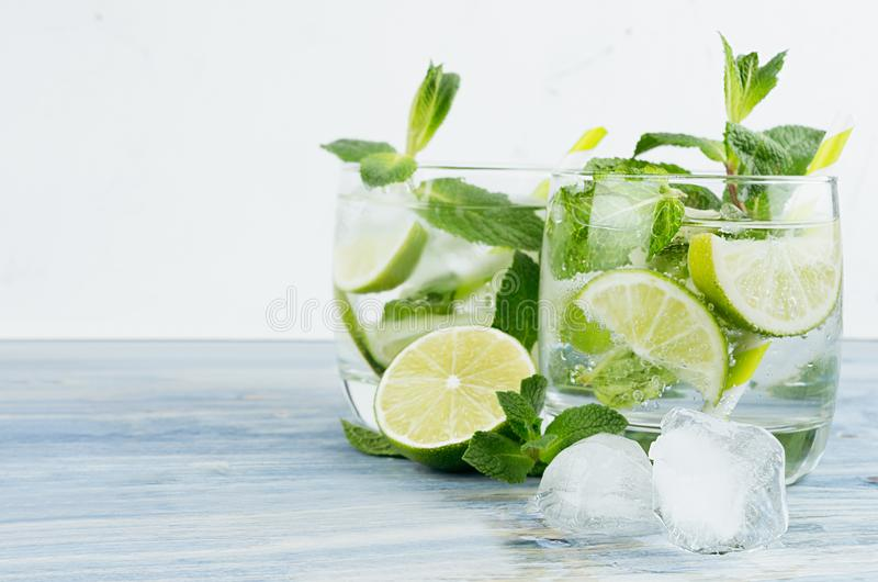 Fresh cold summer beverage gin and tonic with lime, leaf mint, straw, ice cubes, soda on light white background. stock photo