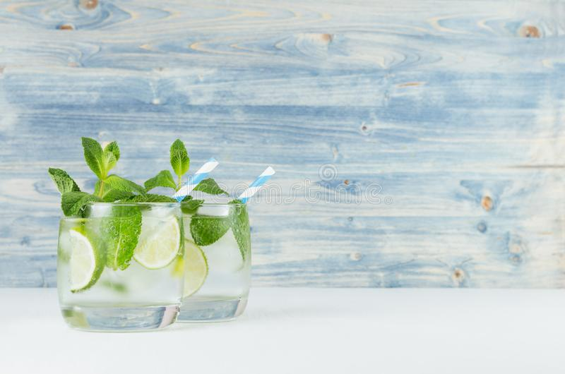 Fresh cold summer beverage with lime, leaf mint, straw, ice cubes on light blue wooden background. Fresh cold summer beverage with lime, leaf mint, straw, ice royalty free stock photography