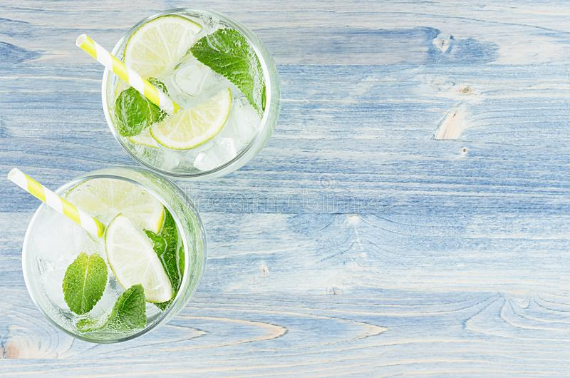 Fresh cold summer beverage mojito with lime, leaf mint, straw, ice cubes, soda on blue wood background, top view, border. royalty free stock images