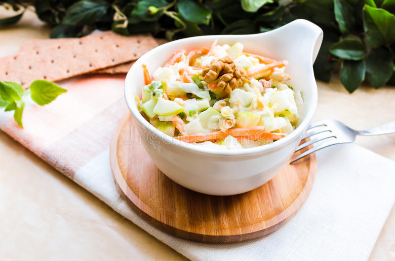 Fresh coleslaw salad with white cabbage, carrot, apples and pears with walnuts and yogurt dressing in a bowl royalty free stock images