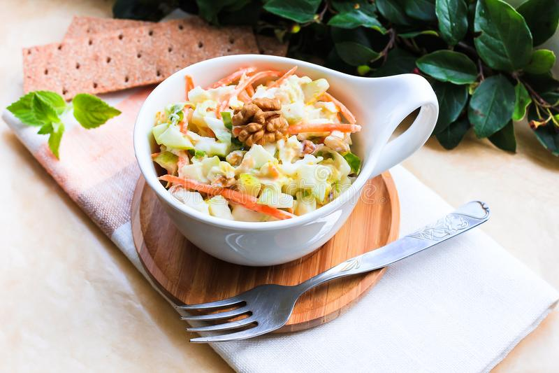 Fresh coleslaw salad with white cabbage, carrot, apples and pears with walnuts and yogurt dressing in a bowl, selective focus. Hea royalty free stock image