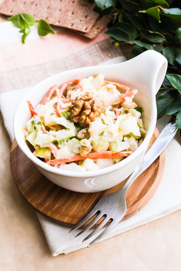 Fresh coleslaw salad with white cabbage, carrot, apples and pears with walnuts and yogurt dressing in a bowl, selective focus. Hea stock photos