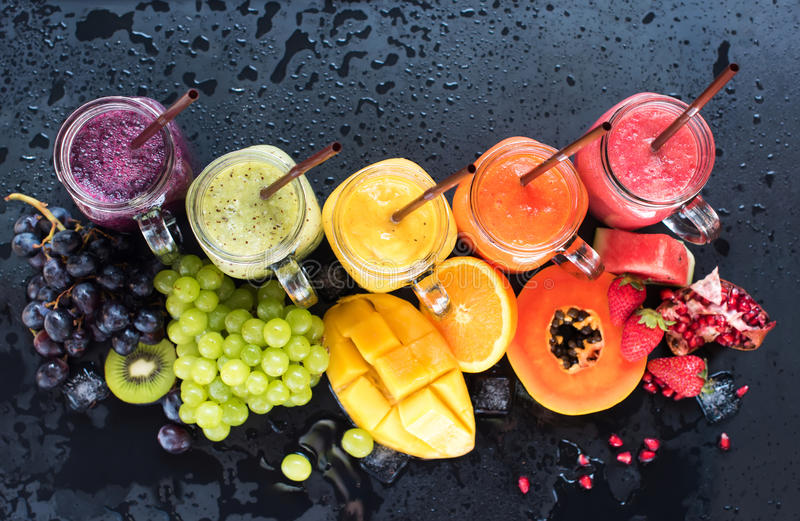 Fresh color juices smoothie tropical fruits royalty free stock images
