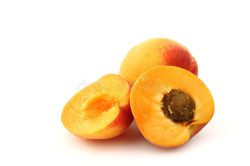 Fresh colorful apricot an two halves. On a white background royalty free stock photos