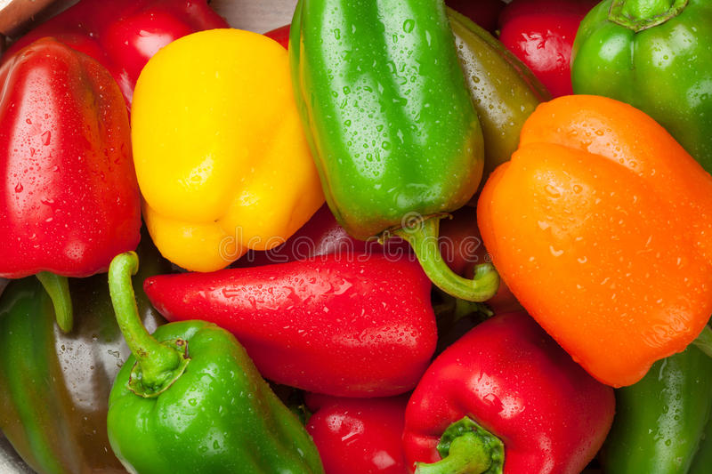 Fresh colorful bell peppers on wooden table royalty free stock photography