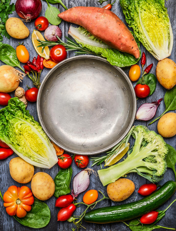 Fresh colorful organic season vegetables ingredients around empty steel plate on rustic wooden background, top view, copy space royalty free stock image