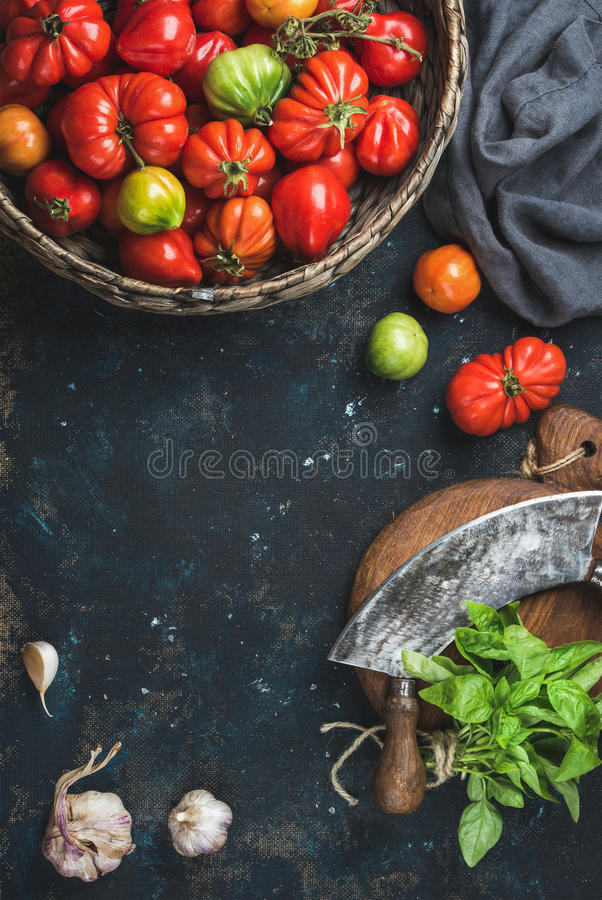 Fresh colorful ripe heirloom tomatoes in basket, copy space. Fresh colorful ripe heirloom tomatoes in basket, basil leaves, garlic, herb chopper knife for royalty free stock photos