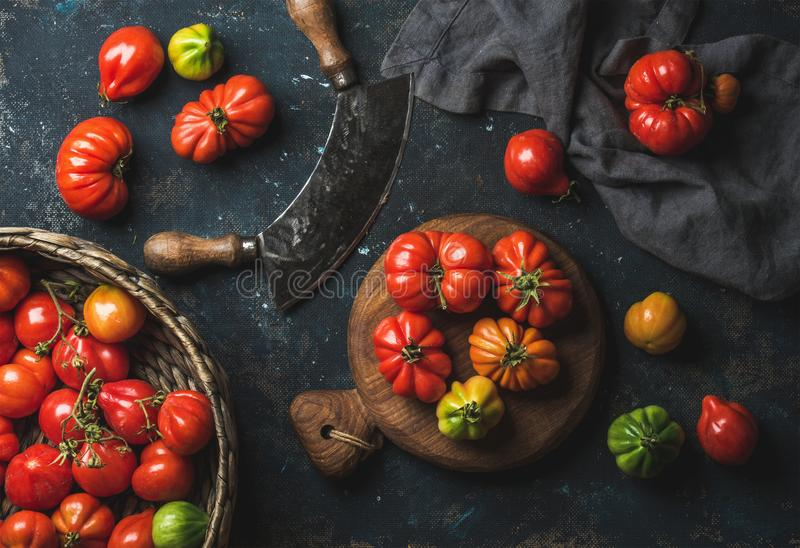 Fresh colorful ripe heirloom tomatoes in basket and wooden board. Fresh colorful ripe Fall heirloom tomatoes in basket and on wooden board, herb chopper knife royalty free stock images