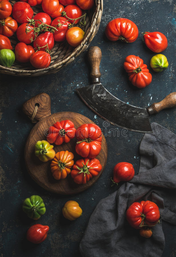 Fresh colorful ripe heirloom tomatoes in basket and wooden board stock photography
