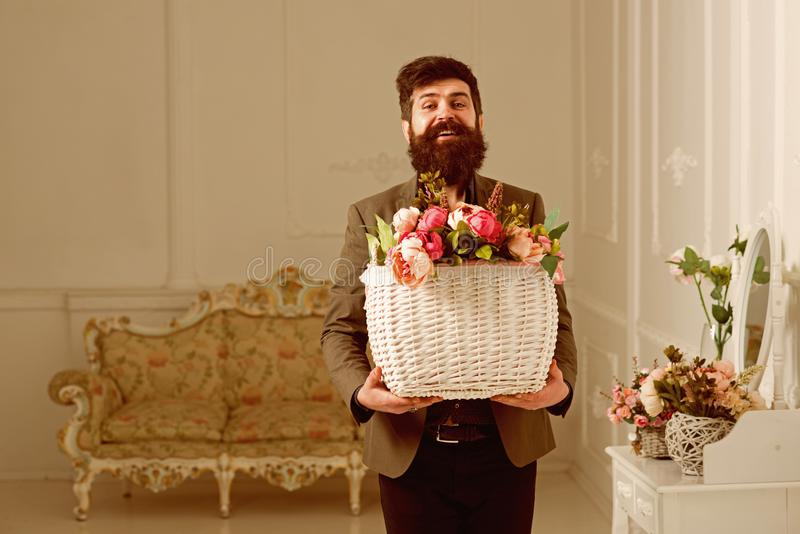 Fresh concept. Bearded man hold basket with fresh flowers. Man smile with fresh floral arrangement. Happy hipster with royalty free stock photography