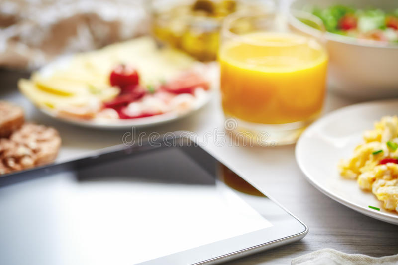 Fresh continental breakfast. Tablet, black screen, selective focus. Concept of business or holiday breakfast. Background, shallow depth of field royalty free stock images