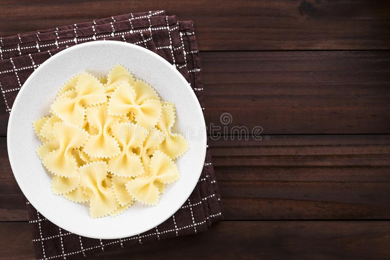 Cooked Farfalle Pasta. Fresh cooked farfalle, bow-tie or butterfly pasta served in bowl without sauce, photographed with copy space overhead on dark wood stock photography