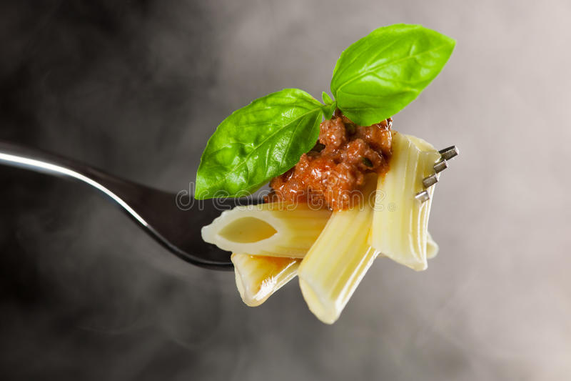 Fresh cooked pasta on fork with bolognese sauce and green basil. Leafs. Hot tasty penne surrounded with steam royalty free stock photo
