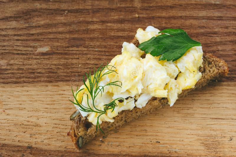 Fresh cooked scrambled eggs with herbs on piece of bread, wooden background. stock photo