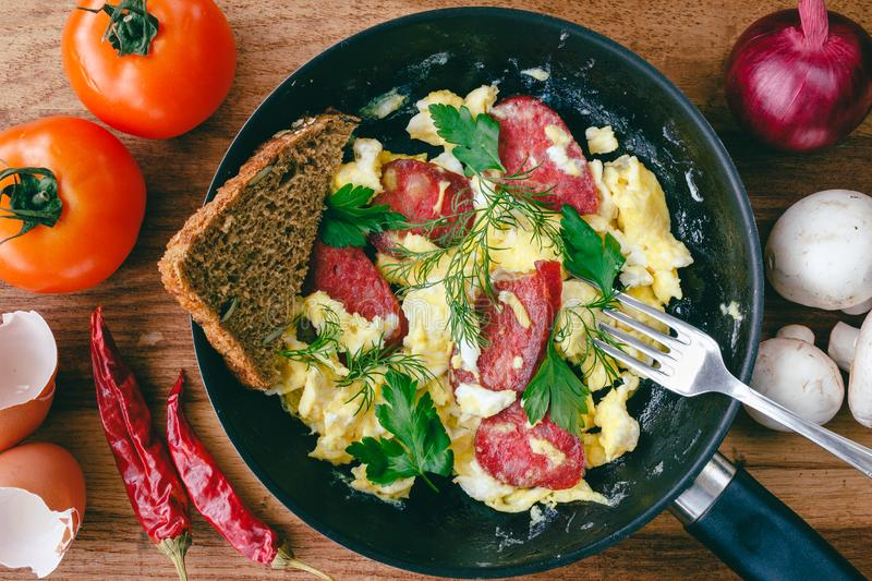 Fresh cooked scrambled eggs in pan with sausage and herbs. Bread, fork, vegetables on wooden board, top view. royalty free stock photography