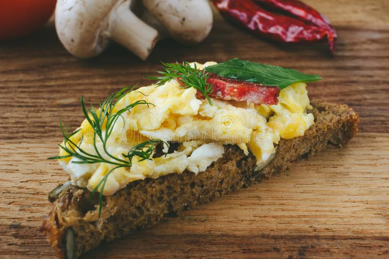 Fresh cooked scrambled eggs with sausage and herbs on piece of bread. mushroom, chilli pepper on wooden background. stock photography