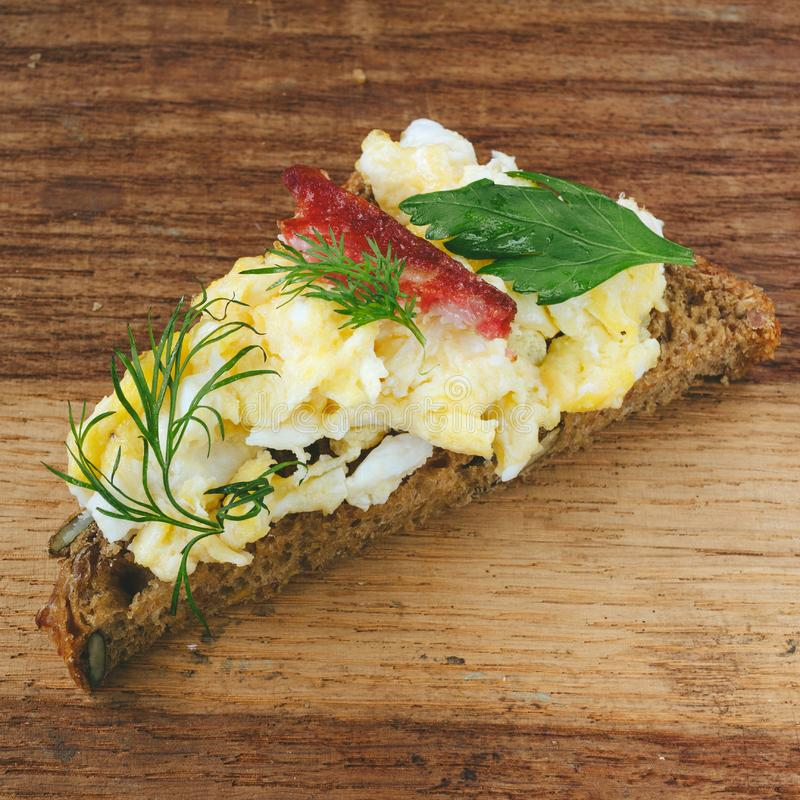 Fresh cooked scrambled eggs with sausage and herbs on piece of bread, wooden background. royalty free stock photo