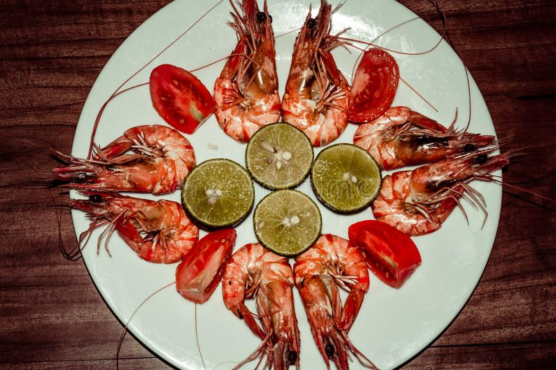 Fresh cooked shrimps with limes, tomatos on white plate. Red prawns. Healthy delicious seafood dinner lunch. Diet concept. Sea royalty free stock photos