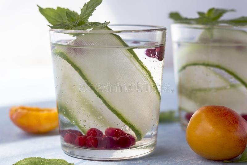 Fresh cool detox drink with cucumber, berries and peaches or aprikotes royalty free stock image
