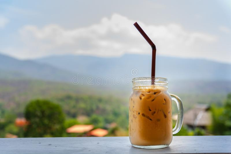 Fresh cool ice coffee cup with mountain background for refreshment in a hot day royalty free stock photos