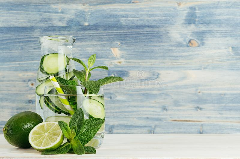 Fresh cool lemonade in bottle and glass with bubbles carbonated water, lime, cucumber, mint, ice on light blue wood plank. stock photography