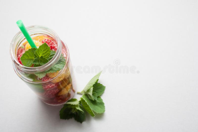 Fresh, cooling drink from the berries of yellow and red raspberries with mint on gray background with empty copy space for a healt stock photos