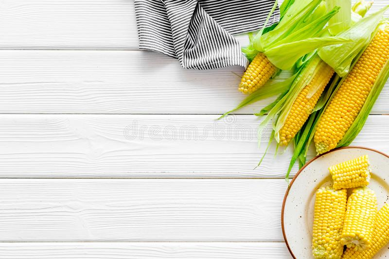 Fresh corn on plate as farm food on white wooden background top view space for text royalty free stock photo