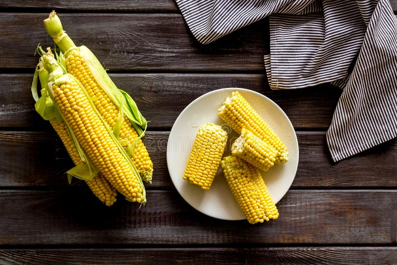Fresh corn on plate as farm food on wooden background top view stock image