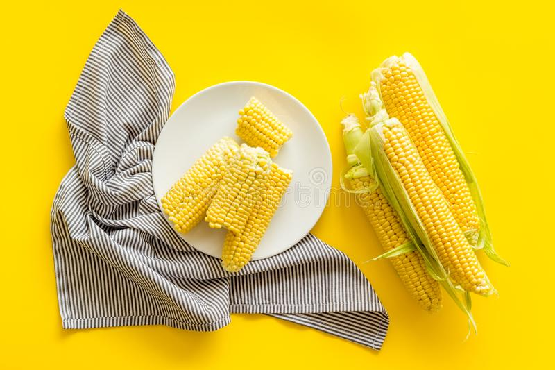Fresh corn on plate as farm food on yellow background top view royalty free stock photos