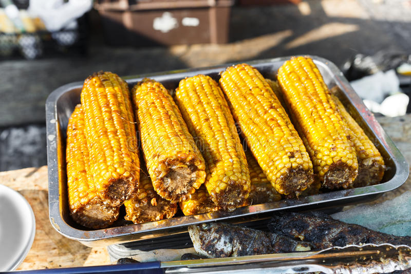 Fresh corncobs cooked at barbecue grill. Vegan bbq party. Barbecue corns outdoors. Cookout bbq vegetable food. Fresh organic, healthy vegetarian grilled snack royalty free stock photo