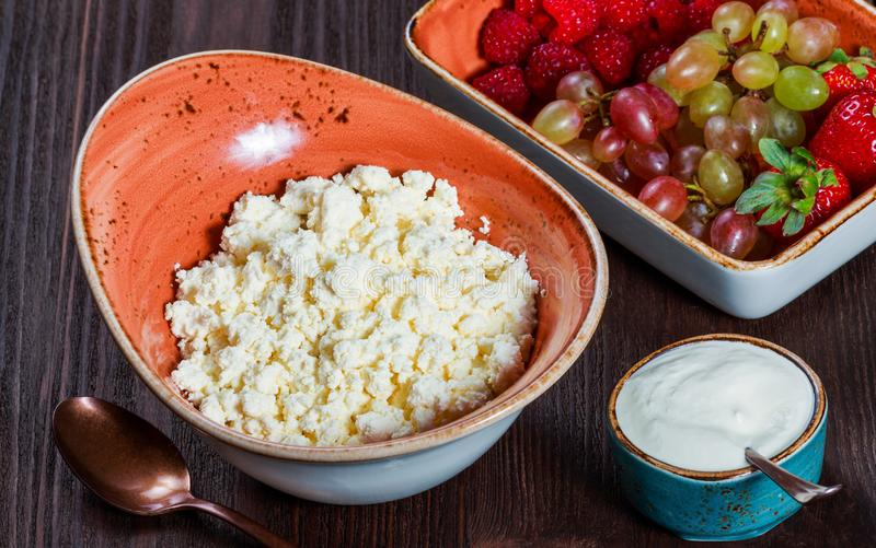 Fresh cottage cheese with juicy berries raspberries, strawberry and grapes on dark wooden background. royalty free stock photography