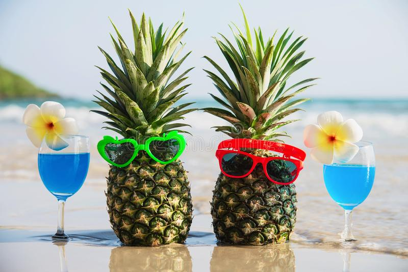 Fresh couple pineapples with sun glasses and cocktail glasses on clean sand beach with sea wave background royalty free stock images