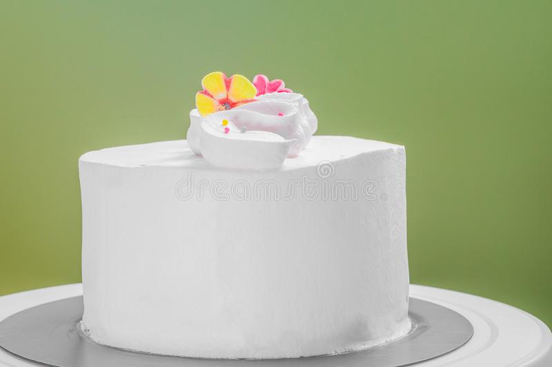 Fresh cream frosted cake with ornament flowers against green background. Fresh cream frosted cake with flowers against green background royalty free stock image