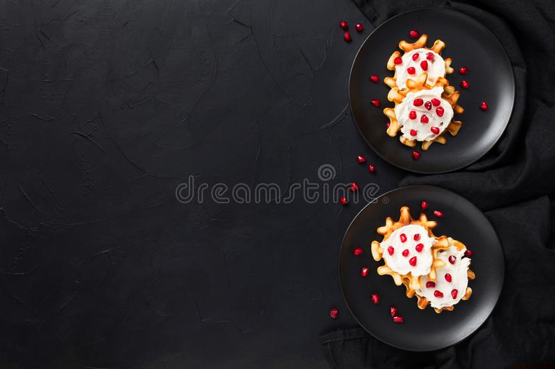 Fresh crispy belgian waffles with cream and pomegranate seeds stock photography