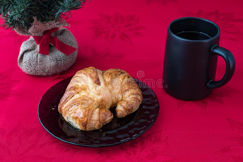 Fresh croissant on a purple glass plate on red tablecloth with black coffee cup. Artificial Christmas tree with burlap root ball and red ribbon stock image