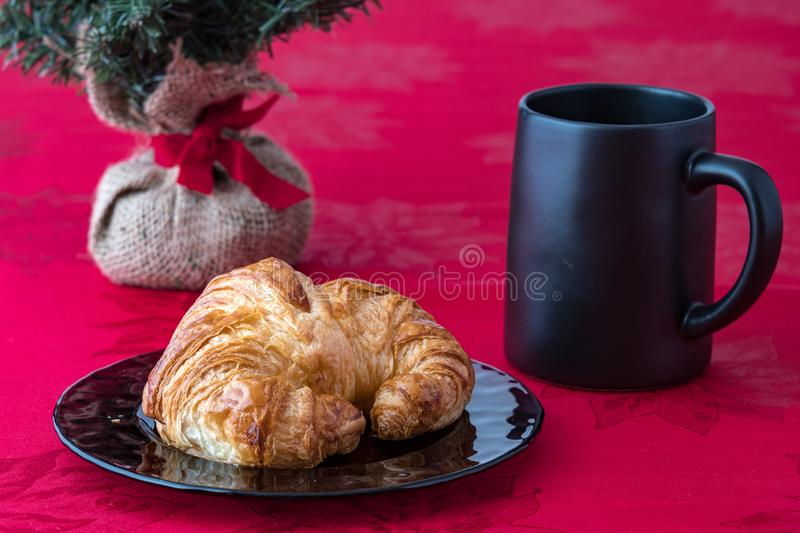 Fresh croissant on a purple glass plate on red tablecloth with black coffee cup. Artificial Christmas tree with burlap root ball and red ribbon royalty free stock photo