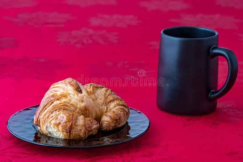 Fresh croissant on a purple glass plate on red tablecloth with black coffee cup. Side view royalty free stock photography