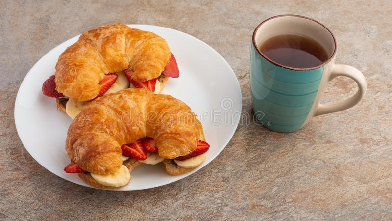 Fresh croissant on the table, with hot tea, strawberries and bananas, delicious breakfast royalty free stock photography